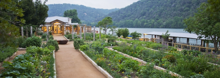 A green garden by the water with several pathways for guests. Green mountains can be seen in the background.