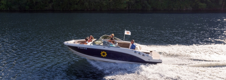 A family skims across the water in a speedboat with the Lake Austin Spa Resort logo on the side.