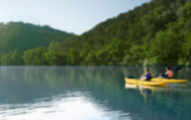 A soft-focus photo of two people kayaking on the water. In the background are two mountains flush with trees.