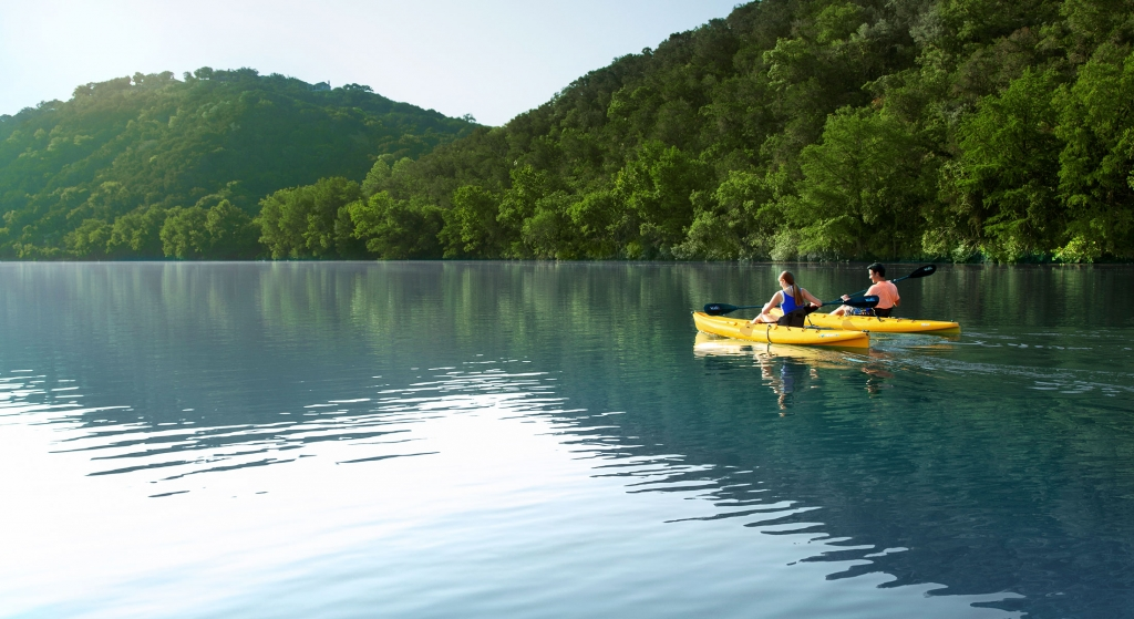 Two people kayaking on the water. In the background are two mountains flush with trees.