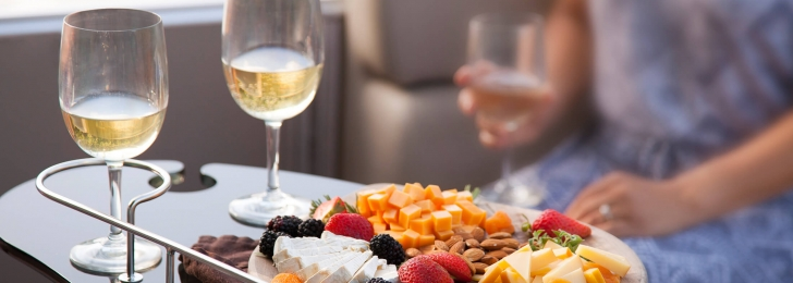 A woman sits at a tray of food consisting of cheeses, almonds, and berries alongside two glasses of wine.