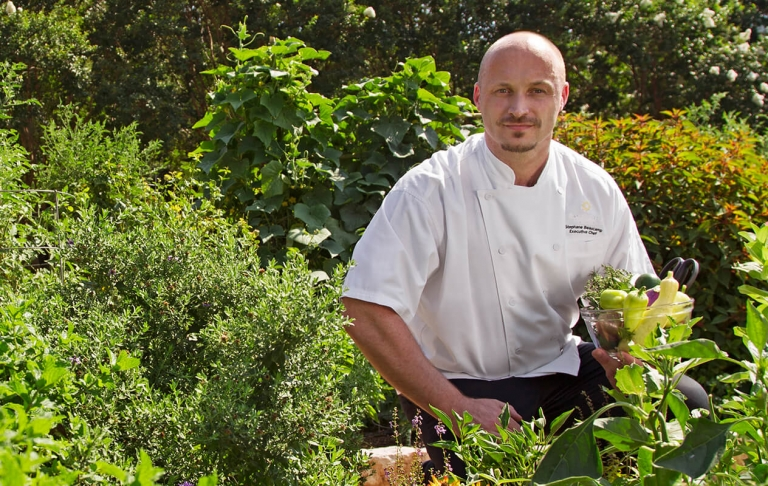 A chef poses for a photo in a beautiful green garden with a bowl of fresh vegetables in his hand.