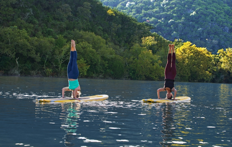 Two women doing headstands on paddleboards in Lake Austin on a sunny day.