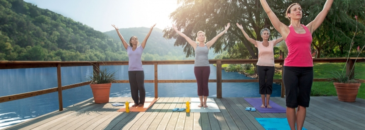 Three women attend a yoga class as their instructor guides them through a series of moves on a deck over the water.