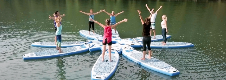 A group of guests perform stretches while standing on their paddleboards in Lake Austin.