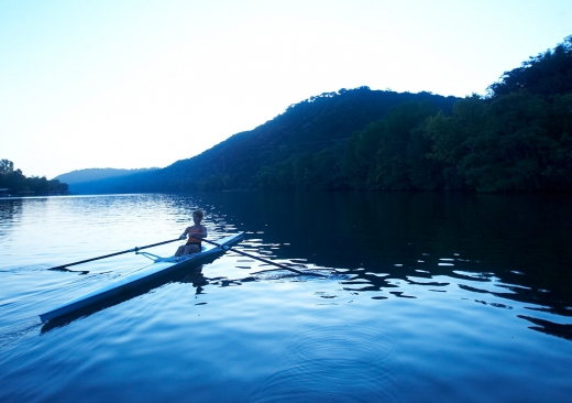 A guest rows in a single scrull rowing boat in the early morning light.