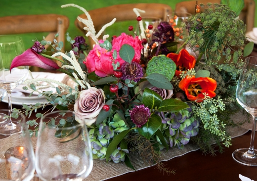 An arrangement of colorful flowers surrounded by wine glasses on a dining table.