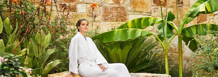 A woman wearing a robe sits in a garden near a small bubbling fountain.