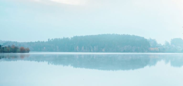 A panoramic shot of Lake Austin on a calm, misty morning