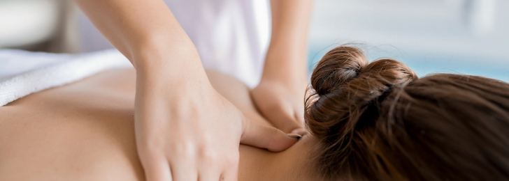 An up-close shot of a woman receiving a neck massage from a professional masseuse.