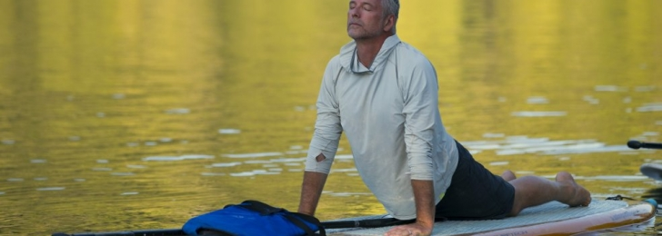 A man does yoga on a standup paddleboard on a calm lake. His body is face down but his torso stretches up into cobra pose.