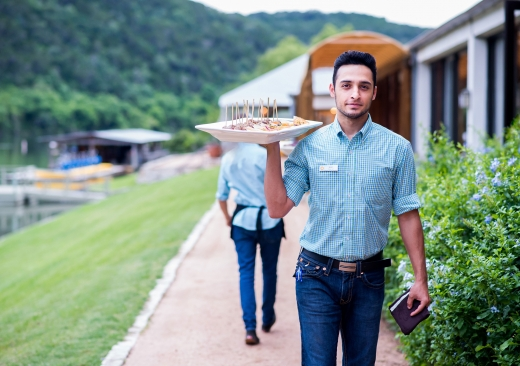 A male server in jeans and a nice checkered shirt carries a tray loaded with hors d'hoeuvres along an outdoor path.