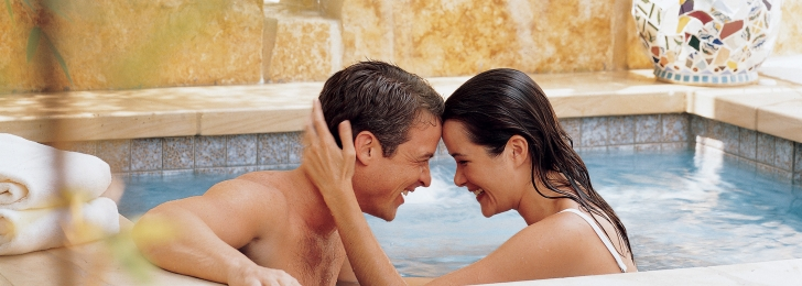 A man and a woman in the hot tub. They are laughing, their foreheads touching, she has her hand on the back of his head.