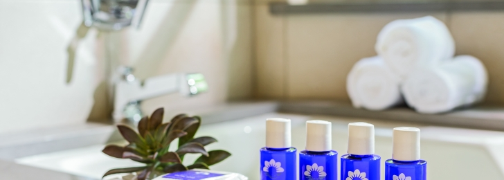 Beautiful blue bottles line the side of a luxurious looking bathtub. There are also towels rolled up and a pretty plant.
