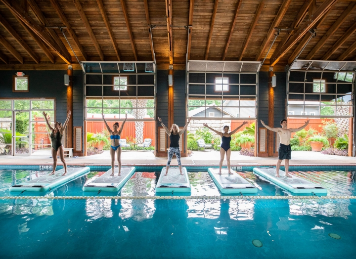 Four people stand on floating yoga mats in a large indoor pool with a view of green gardens in the background.