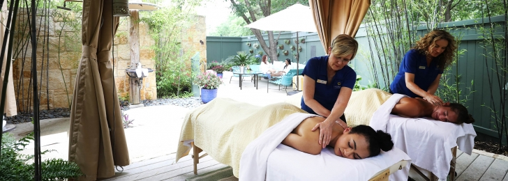 A couple receives a massage outdoors underneath a canopy with gardens in the background.