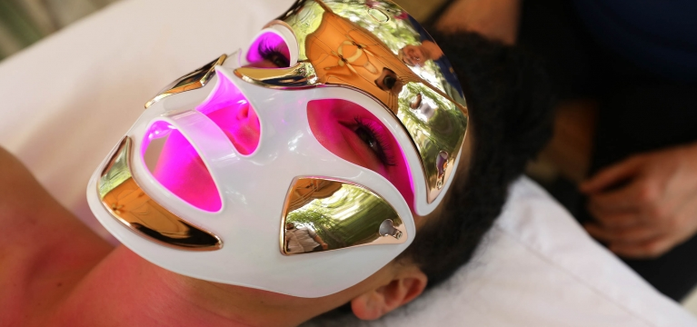 A woman receives a facial enhancement spa treatment wearing a laser therapy mask.
