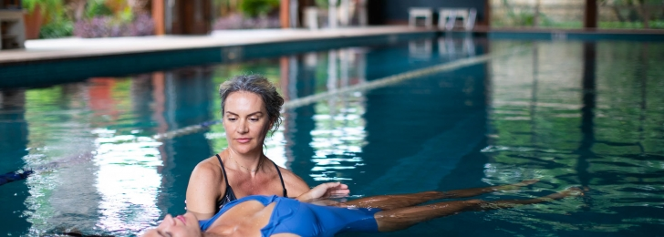 A woman holds another floating woman inside an indoor pool. Lush greenery can be seen in the background.