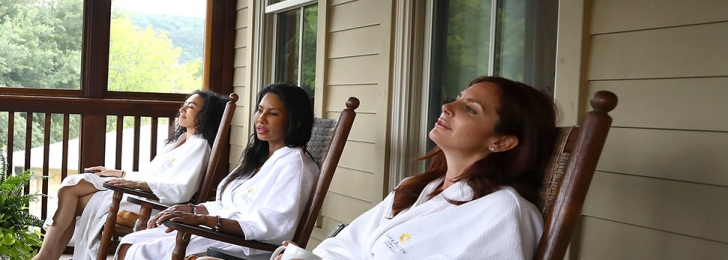 Three women sit on an outdoor porch in wooden rocking chairs all wearing white robes and blue sandals. One woman holds a mug.