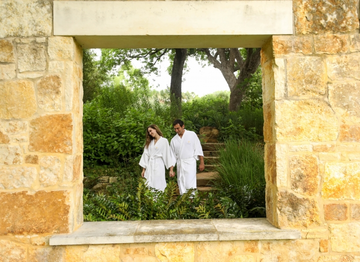 A tan stoned wall with a window where a couple can be seen wearing white robes while holding hands surrounded by greenery.