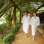 A couple walks under a wooded canopy surrounded by greenery in white Lake Austin branded robes