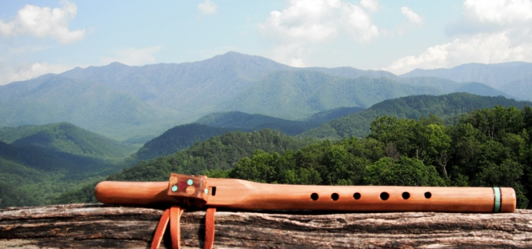 A wooden flute overlooking the lush green mountains and valleys surrounding Lake Austin