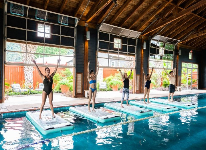 Five people stand on floating yoga mats in the indoor pool during a yoga class.