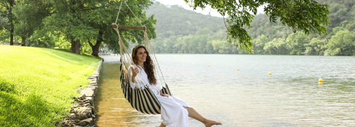 A woman sits in a hammock above the a large lake with a small grassy hill in the background.