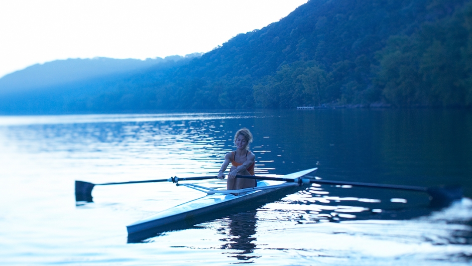 A woman sits in a single person rowboat on a lake at dawn.