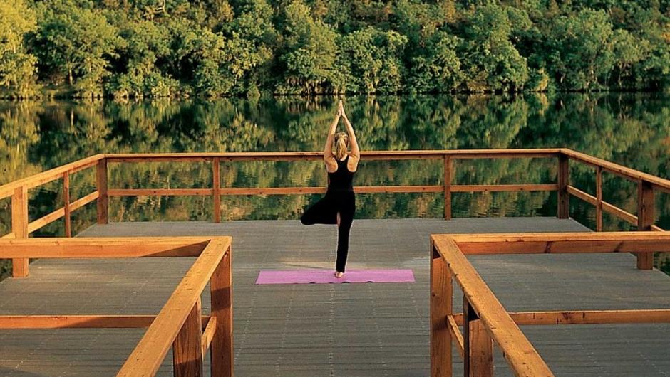 Woman doing yoga on yoga dock