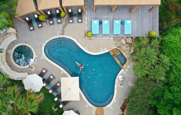 An aerial view of the pool with a woman floating inside it, a hot tub and pool chairs.