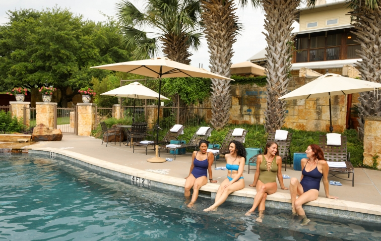 4 women sit poolside with their feet in their water at Lake Austin Spa Resort