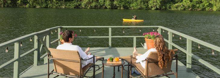 A couple sits on patio furniture on a green wharf facing the lake where a yellow sea kayak can be seen.