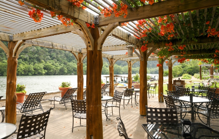 An outdoor patio where tables and chairs sit with a natural wood canopy and orange flowers peaking through its roof.