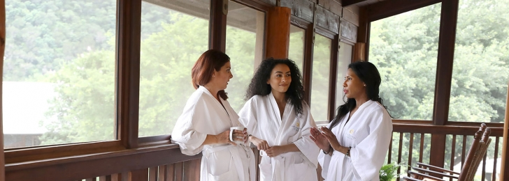 Three women converse on an outdoor porch while wearing white robes. Wooden rocking chairs can be seen in the background.