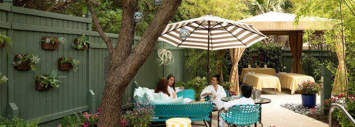 A group of women sit in an outside garden in white robes under a striped umbrella with massage beds in the background.