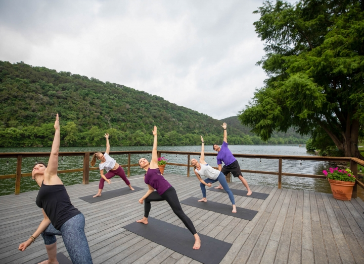 A group of people attend a yoga class on a wharf lakeside. In a lunge position, one arm is extended in the air.
