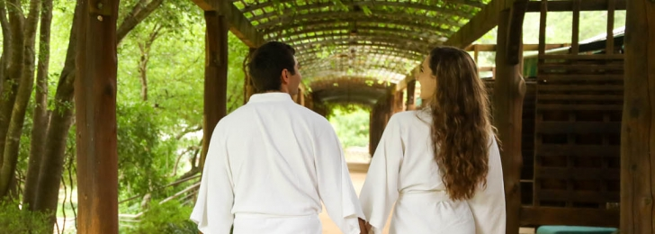 A couple holding hands walk underneath a wooden canopy surrounded by trees while holding hands.