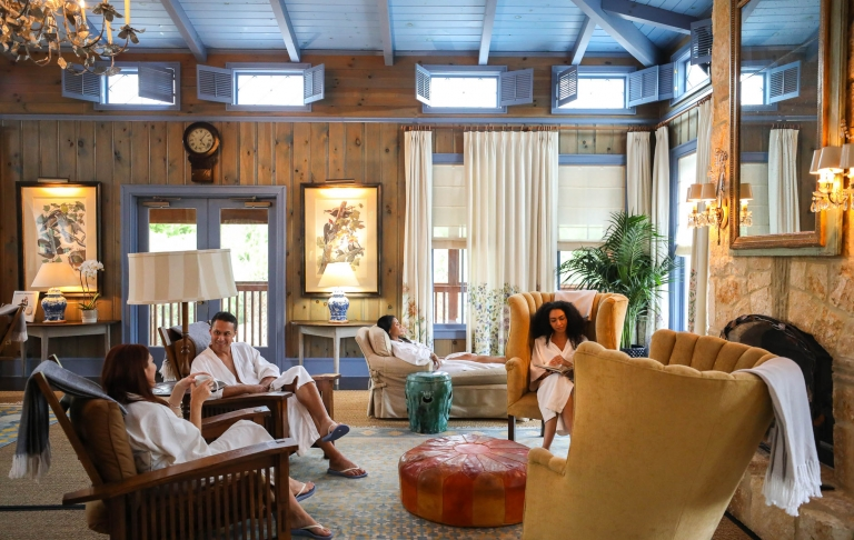 People sitting in the resort lobby in white robes. Natural wood with light blue accents and pastel furniture make the room.