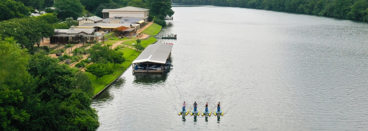 An aerial shot of the lake, resort, and boat house. Four people are on the lake on standup boats.