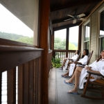 Three women relaxing in bath robes and sitting in chairs on a deck, while looking off into the distance.