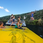 A woman jumping into Lake Austin while her friends smile and watch from the boat.