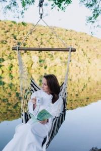 Woman in hammock swing over lake austin