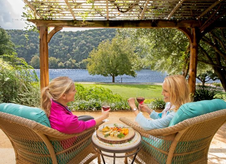 women sitting on porch overlooking lake austin