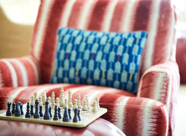 Chess board and plush chairs inside of the living room.