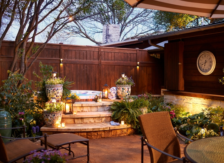 Outdoor garden and hot tub at night in the Lady Bird Presidential Suite.