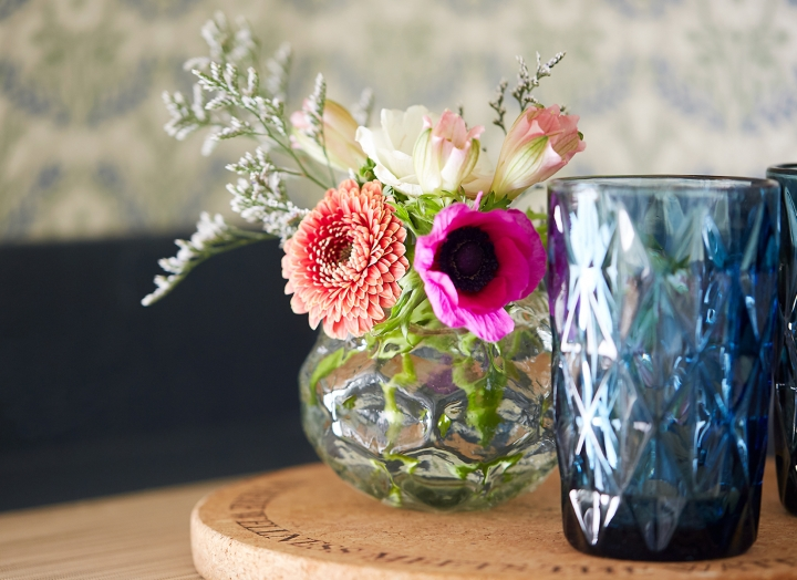 Blue drinking glasses beside fresh flowers.
