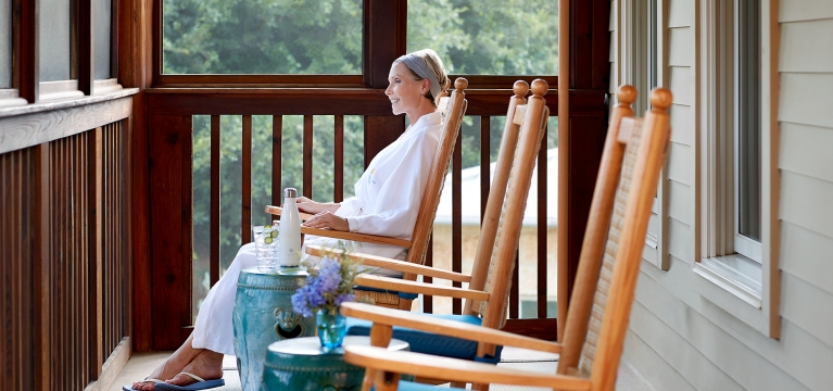 Woman sitting in a rocking chair on the porch of the Blue Room