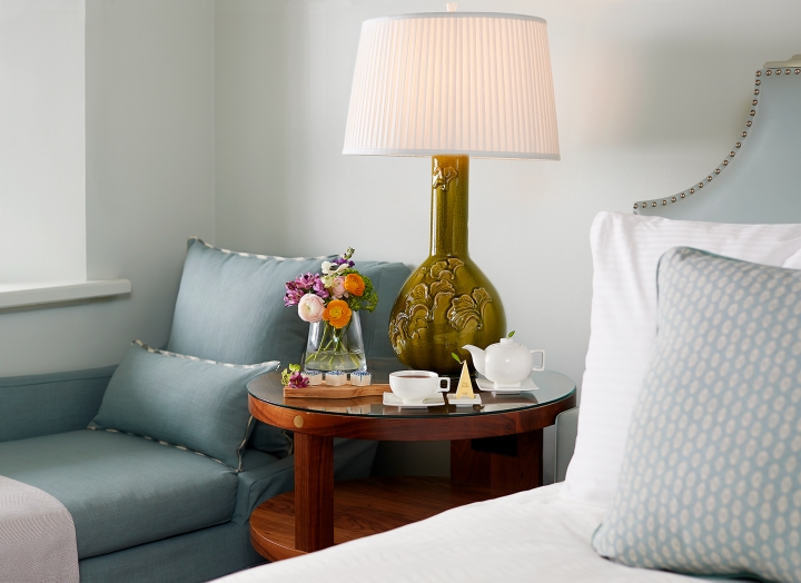 Bedside table with fresh flowers and a lounge chair in the Luxury Garden room