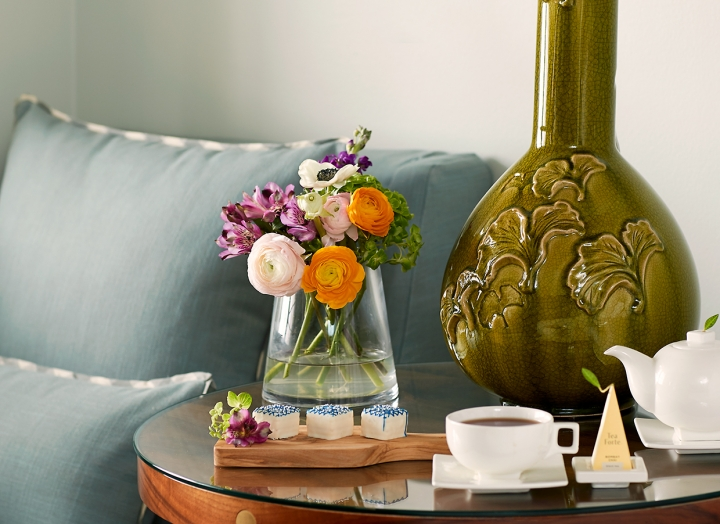 Bedside table with fresh flowers and large green lamp in the Luxury Garden room